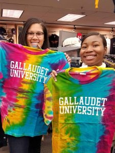 Caroline High students happily showing off tie dye tshirts that say 'Gallaudet University' while shopping at the gift shop at the university.