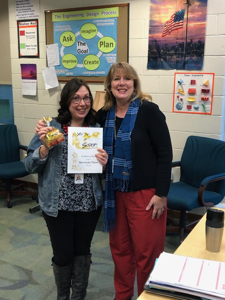 Ms. Tuck stands with director, Mrs. Glass while holding her You're a Star award and bag of sweets.