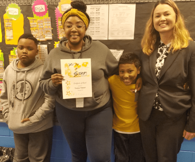 Assistant Principal, Bourgeois, stands with teacher, Tiasia Trent and two students.